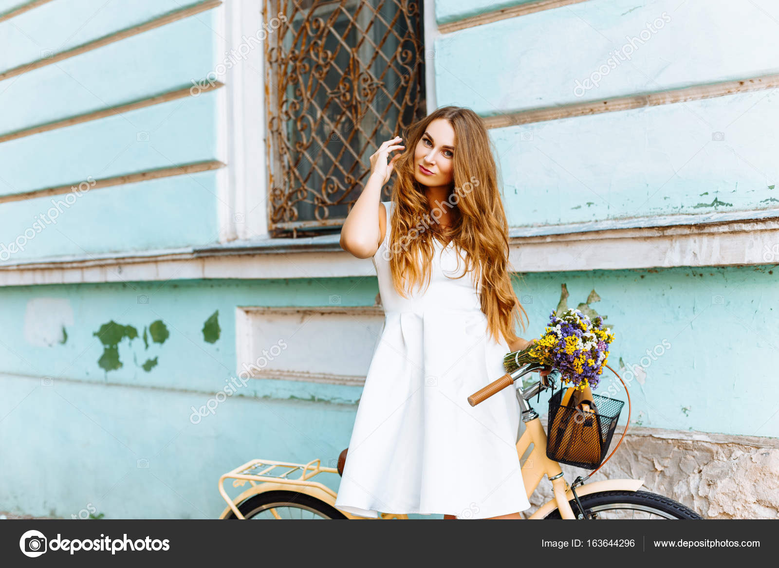 finest selection 8ff9f f60d6 Ragazza in vestito bianco con biciclette e fiori vicino alla ...