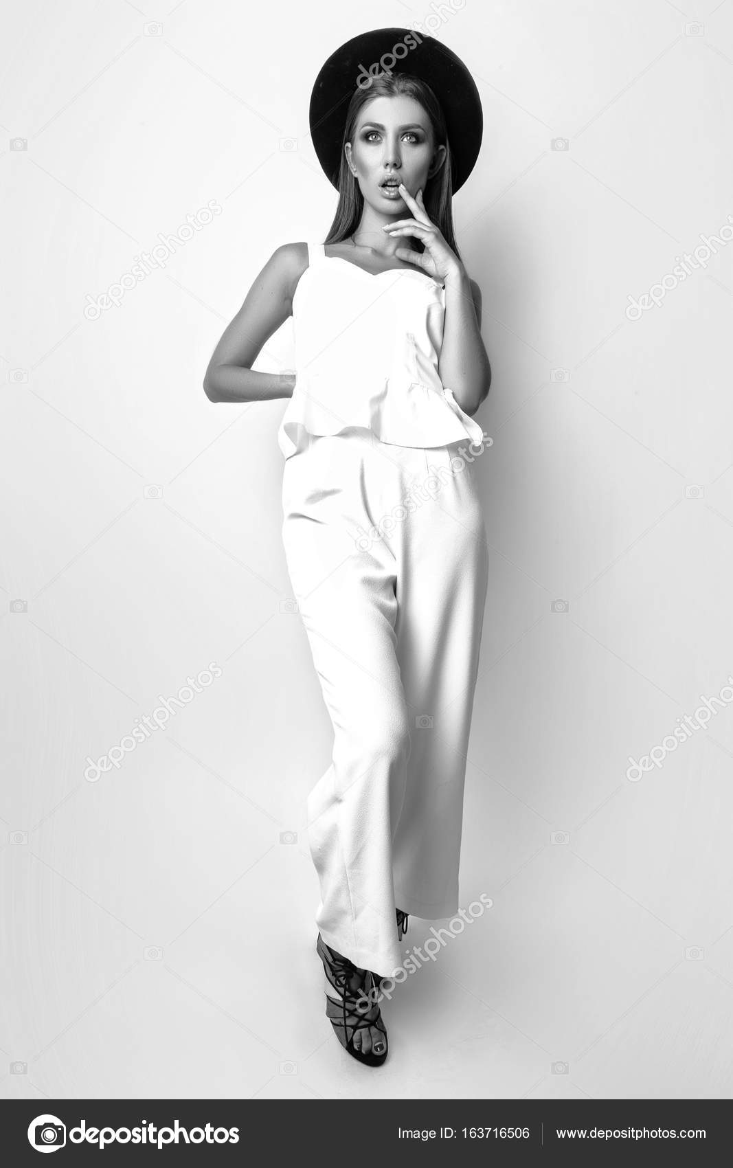 Girl In White Clothes And Black Hat Posing In Studio On White