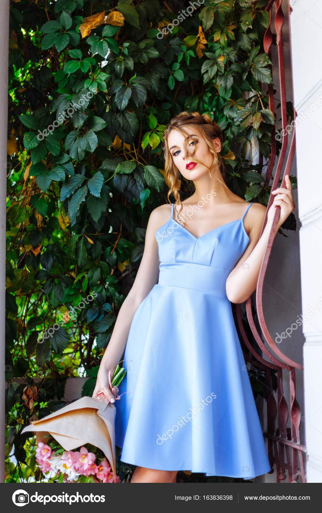 e4b53383d63 Cheerful girl in a blue dress with red lips and a stylish hairdo enjoying a  stroll through the city on a summer sunny day — Photo by ...