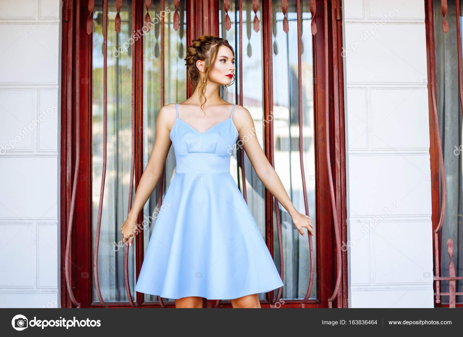 Fröhliches Mädchen in einem blauen Kleid mit roten Lippen und eine ...