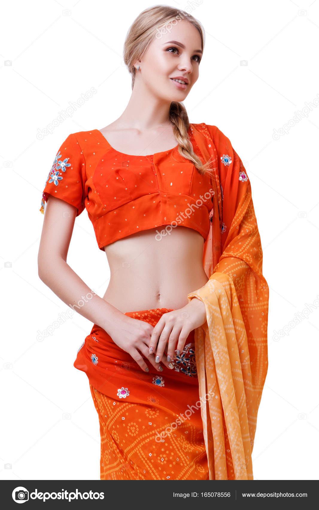 653058ceaa37 Kavkazská blondýna usměvavá dívka v červené indické národní šaty sárí ve  studiu na bílém pozadí