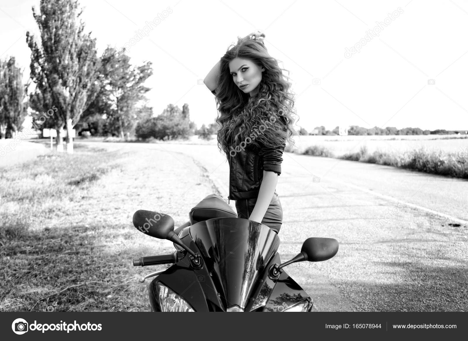 Black and white photo of a beautiful biker girl with a motorcycle stock image