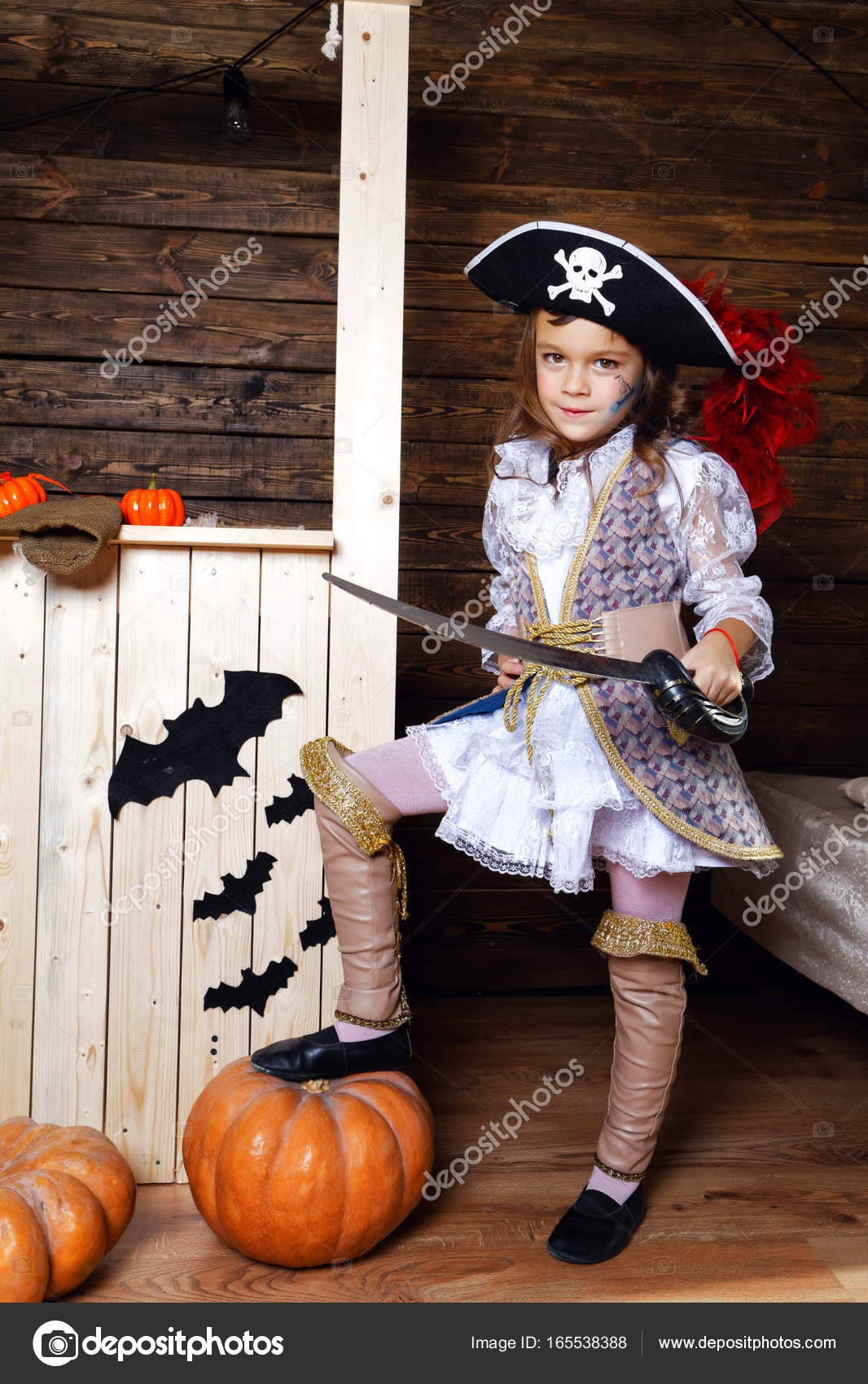 A cheerful pirate girl in a hat and with a saber put her foot on a pumpkin in the studio with scenery for Halloween u2014 Photo by YuliiaChupina  sc 1 st  Depositphotos & Funny girl in pirate costume in the studio with scenery for ...