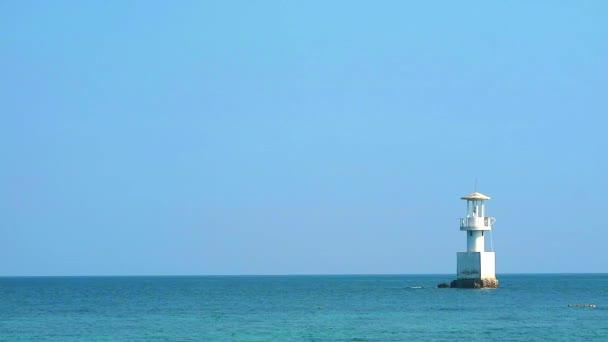 Der weiße Leuchtturm ist von Korallenriffen im Meer und hellem Himmel umgeben