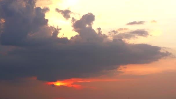 červený západ slunce na vodní hladině moře a tmavý mrak na obloze