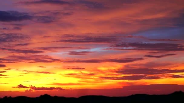 západ slunce červená oranžová žlutá oblačnost obloha na siluetě hory