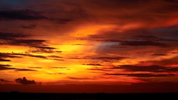 tmavě červený západ slunce na vodní hladině moře a siluety nákladní lodi