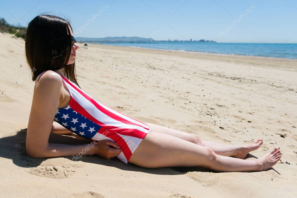 A young woman patriot lies on the beach in a bathing suit the colors of the US flag