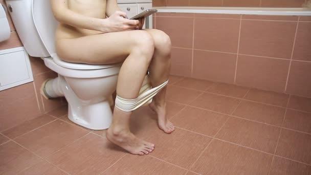 Žena sedí na WC v koupelně. Pomocí chytrého telefonu. Tělo bez oblečení
