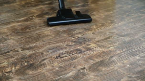 Bürstenstaubsauger bewegt sich auf dem Boden, entfernt Schmutz und Staub. Zeitlupe. 1920x1080