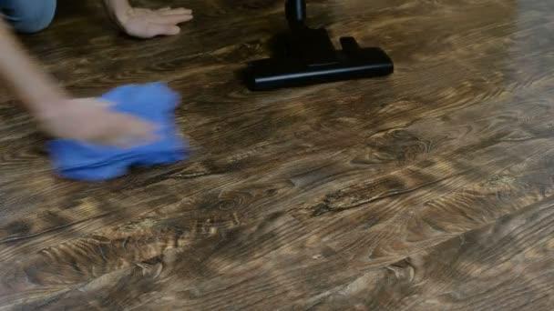 Fans der Reinheit. Ein Mann und eine Frau putzen den Boden und saugen das Laminat. 4k