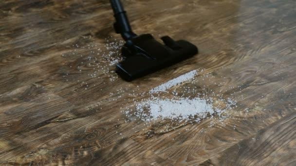 eine Hausfrau benutzt einen Staubsauger, um den Fußboden in ihrem Haus zu reinigen