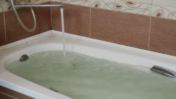 Silný proud vody tekoucí z kohoutku do vany. Plná vana