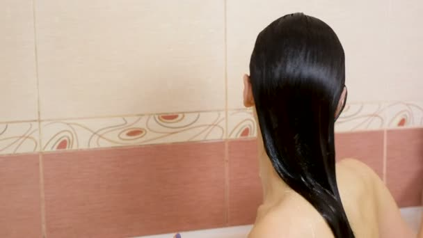 Naked woman brunette pours shampoo from bottle on hand sitting in the bathroom.