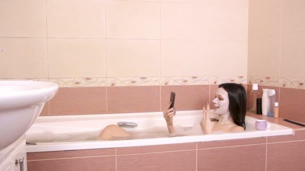 Barna nő arcán maszkot abban rejlik, hogy a fürdőszoba és a gondozás, mobil telefon általános nézet