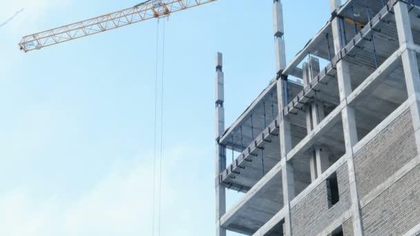 Letecké video boční pohled pod patrové stavebních bloků a stavební jeřáb.