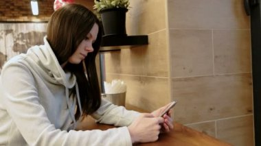 Pensive young brunette woman in a bright shirt reads message in her cellphone sitting in cafe.