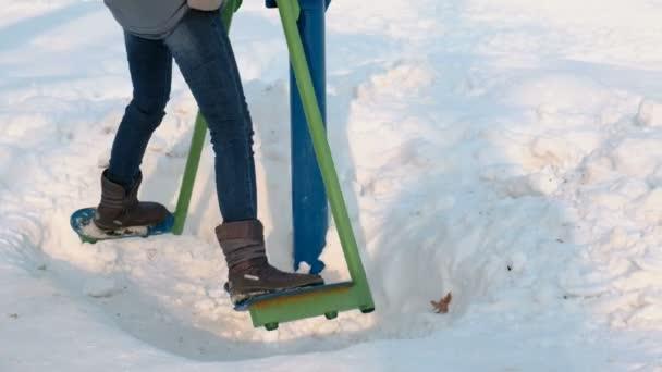 Detail nohy žena dělá nohy cvičení na trenažéru v zimní Park ve městě. Boční pohled