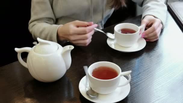 Detail Zenske rukou míchá s lžící cukru v čaji. Konvice a hrnky na stole