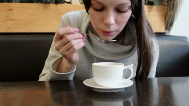 woman drinks hot tea from cup with a spoon. Close up hands and face.