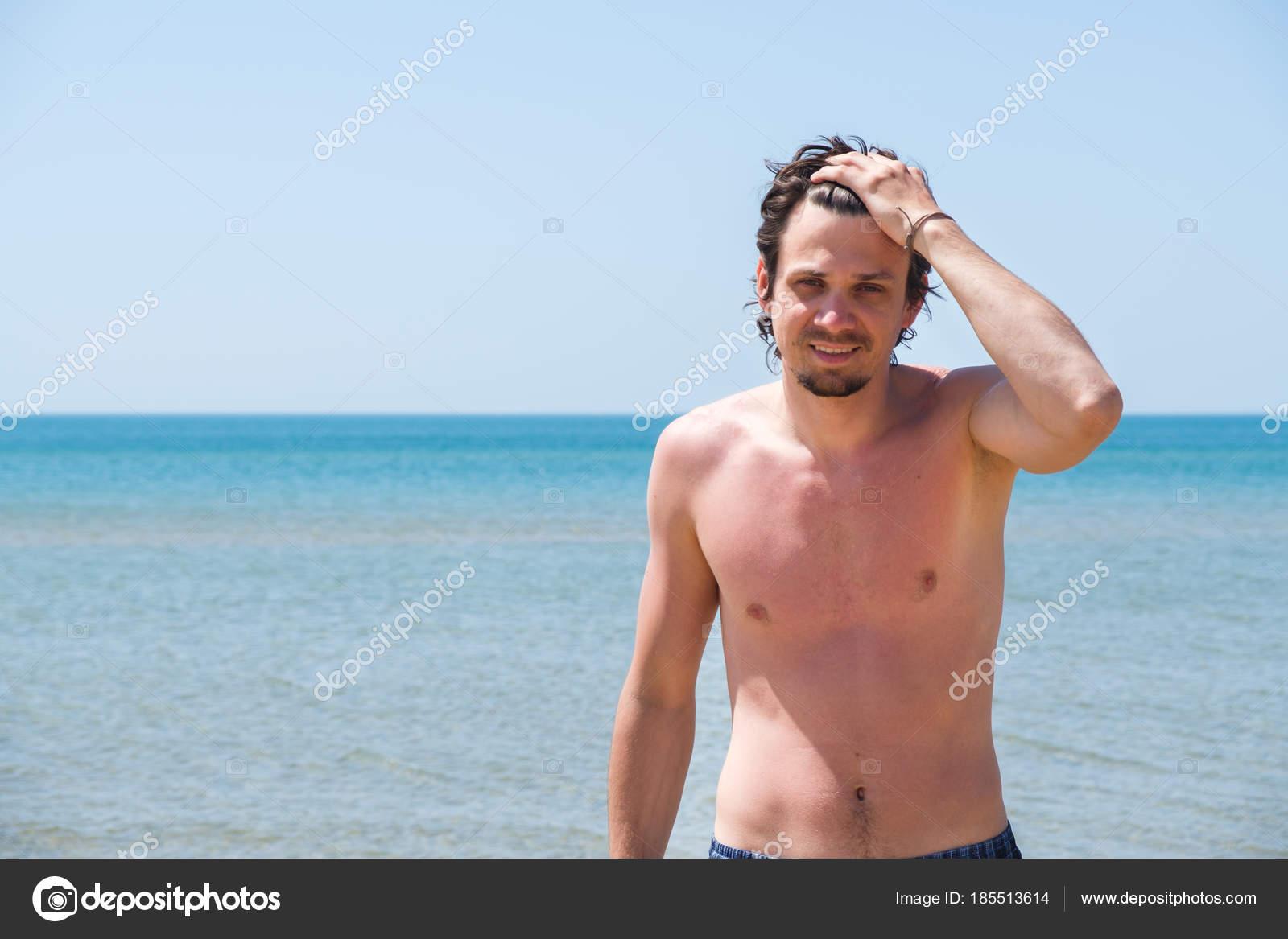 9435e80a0886 Uomo bello che propone sulla spiaggia, ritratto. Mano in capelli. — Foto  Stock