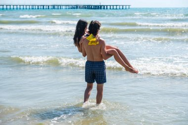 Unrecognizable pair of brunettes. Man carries a woman in his arms at sea.