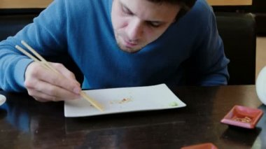 Bruneta mladý muž v modrém svetru jí drobky z desky a olizuje deska s jazykem