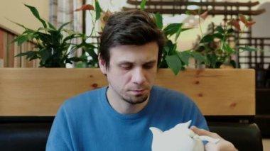 Mladý muž bruneta pohled na konvice na čaj a nápoje z hubičky a usmívá se. Pohled zepředu