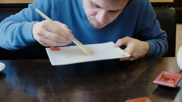 Bruneta mladý muž jí drobky z desky a olizuje deska s jazykem. Pohled zepředu