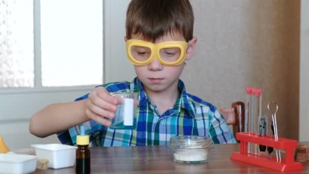 Experimente zur Chemie zu Hause. Nahaufnahme Jungenhände mischen die Substanzen und die blaue Flüssigkeit im Becher.