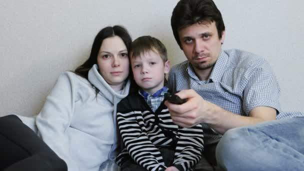 Néz Tv. fiatal család anya, apa és fia együtt Tv figyel. Apa kapcsolók csatornák