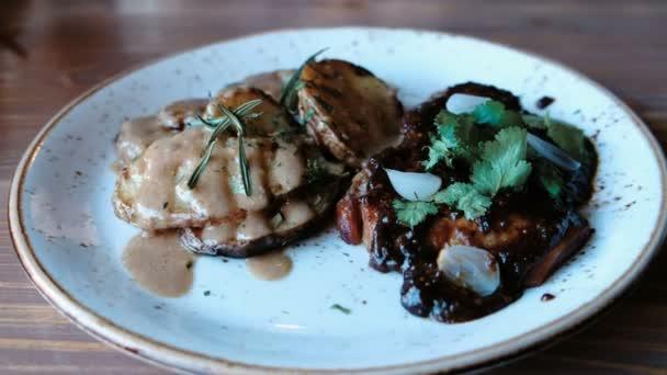 Kus vepřového masa vařené na uhlí s brambory, omáčku a zeleninu na talíř, boční pohled