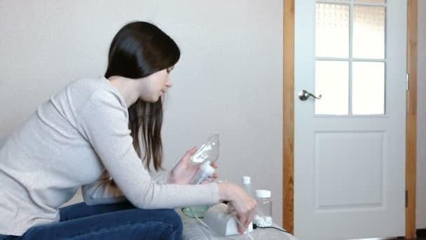 Verwenden Sie Vernebler und Inhalator für die Behandlung. Junge Frau durch Inhalator Maske einatmen. Seitenansicht