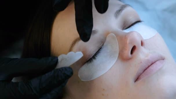 Kosmetické ošetření. Kosmetička se drží natáčky řasy na víčkách žen