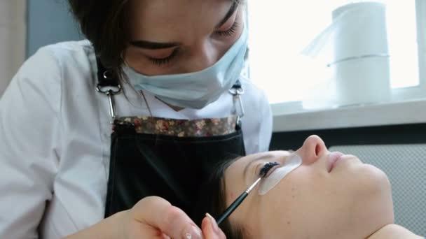 Kosmetické ošetření. Kosmetička klade černé barvy na řasy. Botox a laminování řasy