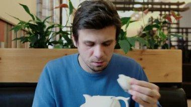 Mladý muž bruneta pohled na čajník a nápoje z hubice a zamračení. Pohled zepředu