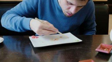 Bruneta mladý muž jí drobky z desky a olizuje deska s jazykem