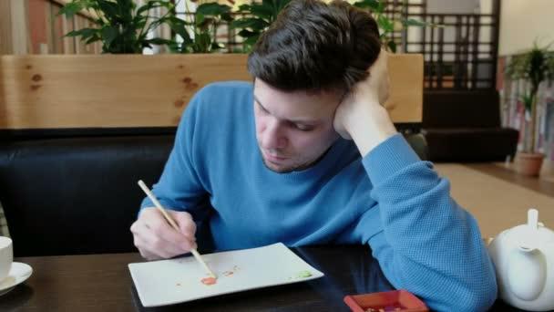 Bruneta mladý muž v modrém svetru shromažďuje přežitek jídlo od desky a dřevěné hůlky