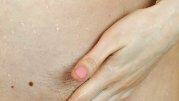 Not shaved close-up of pubic hair on the female body. Woman takes a shower.