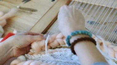Weaving on a loom. Weaving on a loom. Closeup womans hands running on a loom. Threading the needle through the strands of frame
