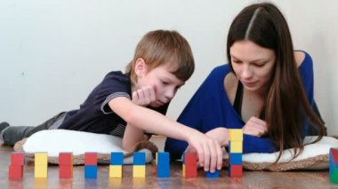 Building a small and big towers from blocks and cubes. Mom and son playing together with wooden colored education toy blocks lying on the floor