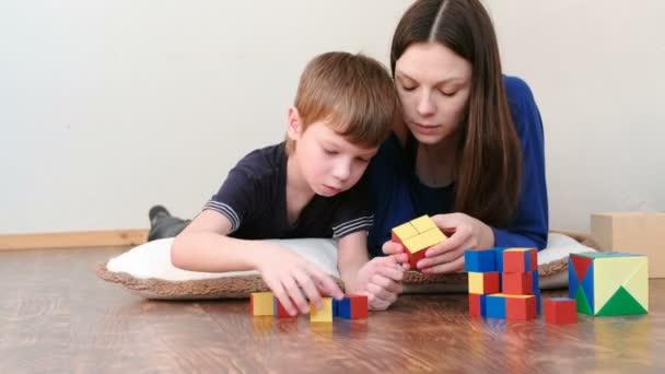 Máma a syn spolu hrají dřevěné barevné vzdělávání hračka bloky ležet na podlaze