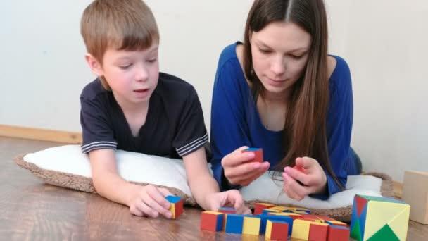 Učení barev a tvarů. Máma a syn spolu hrají dřevěné barevné vzdělávání hračka bloky ležet na podlaze