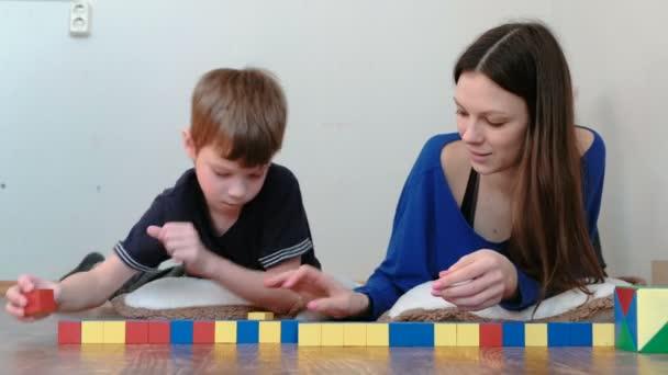 Maminka a syn, práce s bloky hračka dřevěné barevné vzdělávání ležící na podlaze. Šířit kostky v jednom řádku.