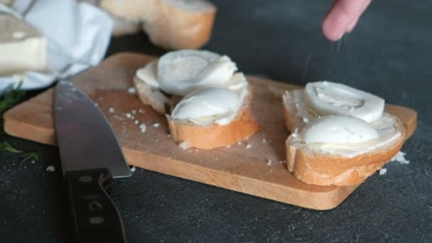 Mano di Womans salate panini con pane, burro e uova su tavola di legno nella priorità bassa nera. Facendo un panini