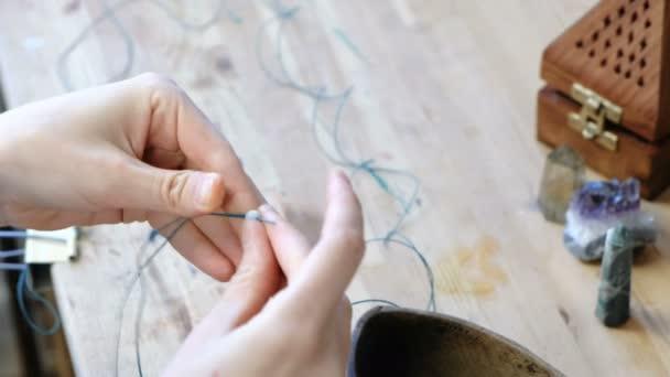 Tkaní korálků. Detail Zenske ruce, navlékání korálků na podproces, takže šperky v dílně. Pohled shora