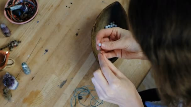 Tkaní korálků. Detail Zenske ruce, navlékání korálků na podproces, takže šperky v dílně. Pohled zezadu