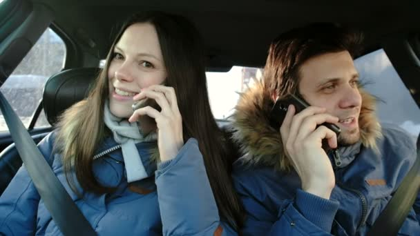 Man and woman speaking their cellphones and laughing sitting in car. Front view