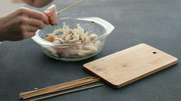Closeup Zenske rukou vaření marinovaný šašlik nebo šíš kebab, kuřecí maso na dřevěné špíz s cibulí na dřevěné desce, zblízka.