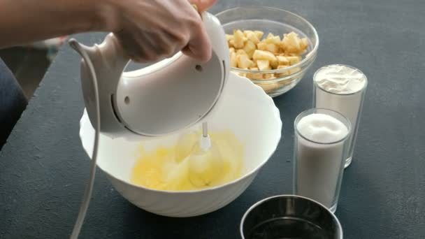 Die Hände der Frauen in Großaufnahme mit einem Mixer verquirlen die Eier in einer Schüssel und fügen Zucker hinzu. Apfelkuchen kochen.